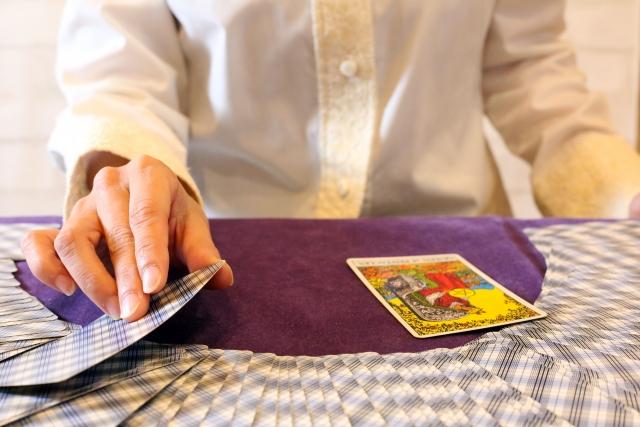 占い師がカードをめくっている画像