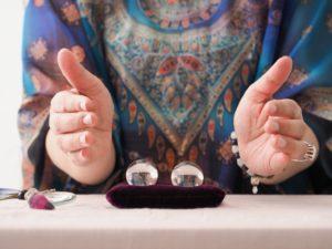 水晶に手をかざしている占い師